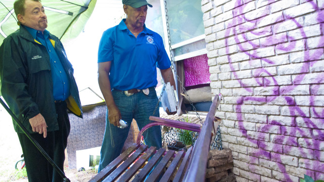 From left, Charles Locke, superintendant, and Ron Pollard, municipal code officer for the City of OKC, chick out a back porch where vagrants have been hanging out at a vacant property at 1324 SW 43rd Street.  (Mark Hancock)