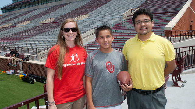 From left, Madeline Siegel of Big Brothers and Sisters, mentee Logan Mejia, and his mentor Rolando Castellanos, at Memorial Stadium for Sooners Media Day. (Mark Hancock)