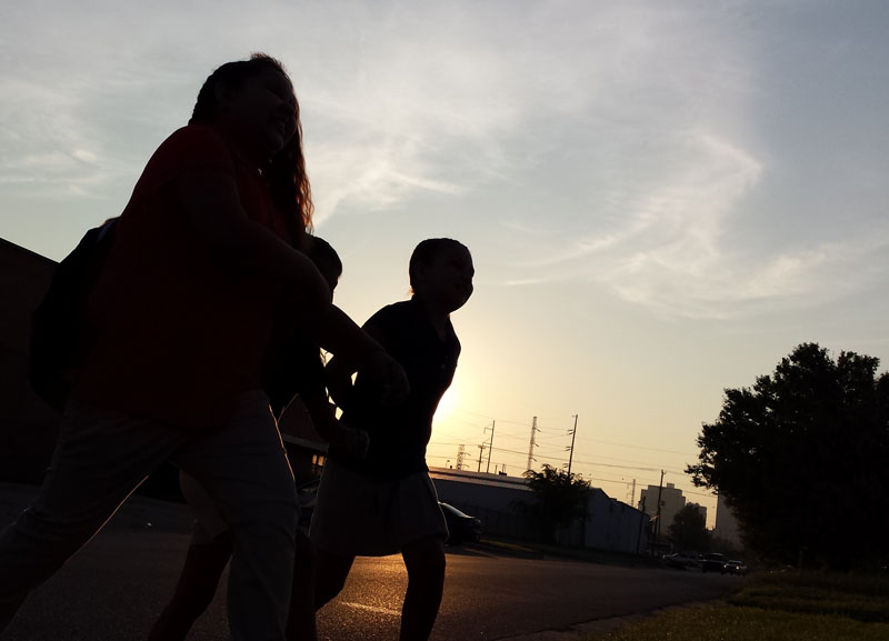 Students walk to the bus stop on the first day of class in the early morning hours on Aug. 4, 2014. (Ben Felder)