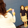 A mother takes a photo of her daughter and friend during the first day of school at Mark Twain Elementary. (Ben Felder0