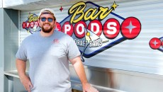 Hunter Wheat stands in front of Bar Pods Draft Bars, a permanent food vendor at The Bleu Garten. (Shannon Cornman)