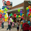 Balloons outside Photo Art Studio add even more local color to Plaza Fest, celebrating it's 16th birthday Saturday.