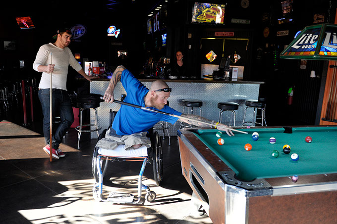 "Chris ""Maverick"" Richardson takes a shot while Shane Cox looks on at Lumpy's Sports Grill on May Avenue. (Garett Fisbeck)"