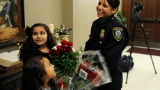 Alma Deloera recieves flowers from her daughter, Tatiana, 7, and her niece, Belle Reyna, 6, after the Oklahoma City Police Academy Recruit Class 132 graduation at First United Methodist Church, Thursday, Dec. 4, 2014.  (Garett Fisbeck)