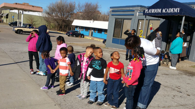 Angela Billings brings a class from Playground Academy daycare out to 23rd Street to watch a march on Martin Luther King, Jr. Day. (Ben Felder)