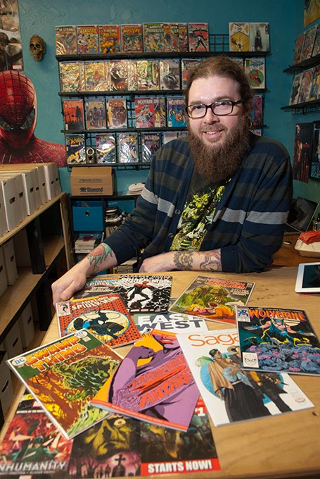 with an assortment of comics at his shop on NW 23rd, next to Pizza 23.  mh