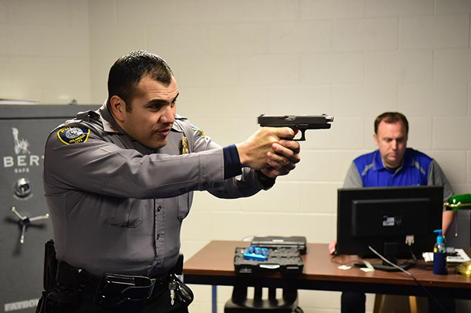 Juan Balderrama draws a CO2 pistol during a police training simulation as Shawn Byrne controls the scenario from a computer. (Mark Hancock)