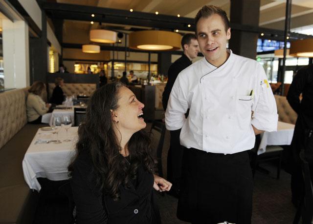 Jeff Dixon, Broadway 10 Bar & Chophouse co-owner, speaks with Terri Sadler of Fitzsimmons Architects, at the restaurant.  (Garett Fisbeck)