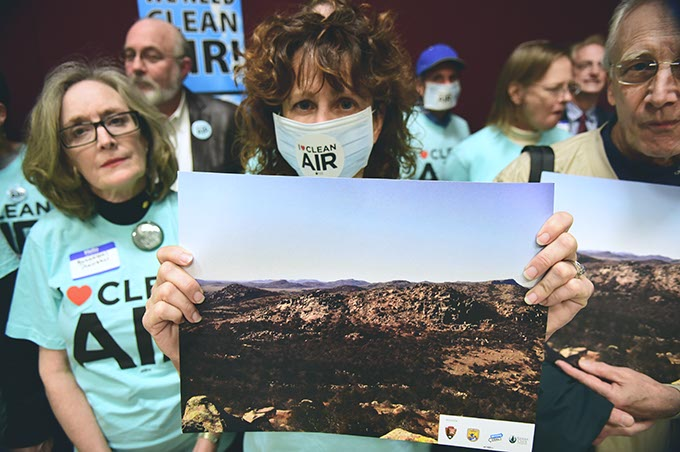 Shelly Campbell holds a photo of the Wichita Mountains with other Sierra Club members. The Wichita Mountains have experienced an increase in air pollution coming from Texas. (Mark Hancock)