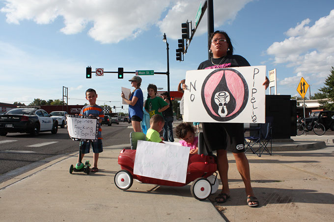 Cleveland County resident Maria Todd stands with her children and a group of demonstrators opposed to the Plains All American Pipeline running through south central Oklahoma. Demonstrators stood at Norman street corners on Sept. 7.  (Laura Eastes)